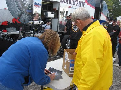 Pam signs a photo... She also backed up the US Male funny car in the second round, much to the delight of the fans.