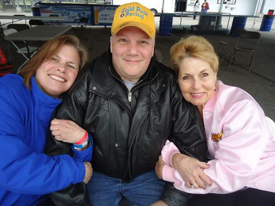 Jim 'Bandit' Folkie gets hugged up by legendary drag strip darlings Jungle Pam Hardy and Bunny Burkett.