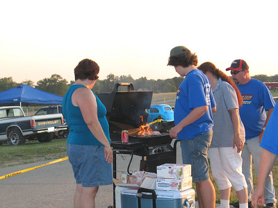 Chef Jason cooks up dozens of hamburgers, while mom Denise, Cheryl and Jerry look on.