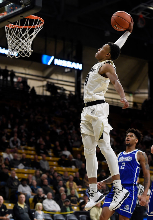 . BOULDER, CO: November 13: University of Colorado\'s  Shane Gatling gets a break way dunk past Drake\'sTremell Murphy  during the game with the Drake Bulldogs. (Photo by Cliff Grassmick/Staff Photographer)