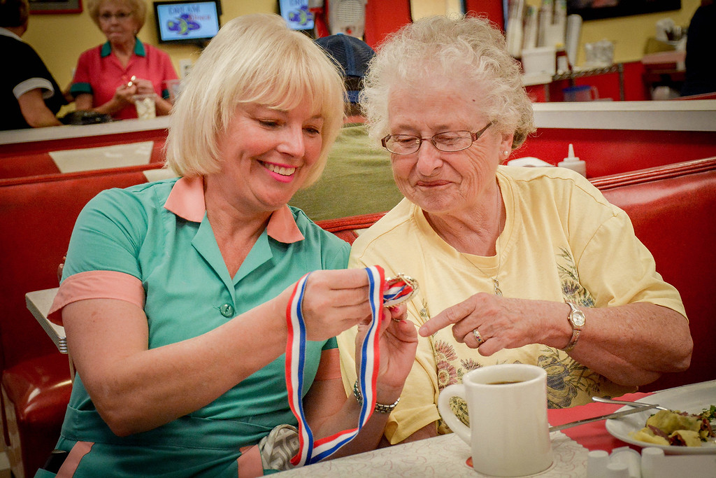 ". At left, Dream Diner owner Marybeth Shanahan gives Virginia ""Cookie\"" Christiana of Nashua a medal for being such a loyal customer for the past 20 years. SUN/Caley McGuane"
