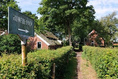 Het pad tussen de keuterijen met aan het einde deels hunebed D3. D4 ligt erachter. Links het bronzen bord