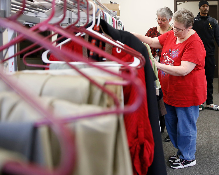 "HOLLY PELCZYNSKI - BENNINGTON BANNER Cindy Butler, of Bennington looks through clothing options during the ""dress for success"" event held at the Bennington Free Library. The event, held to teach others what is interview appropriate and get them prepared when meeting with prospective employers"