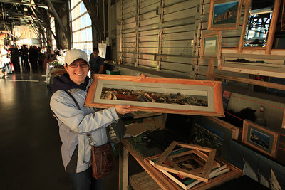 A happy customer pics up her new and very unique panoramic frame with an image 10 frames wide of Peggy's Cove, Nova Scotia.