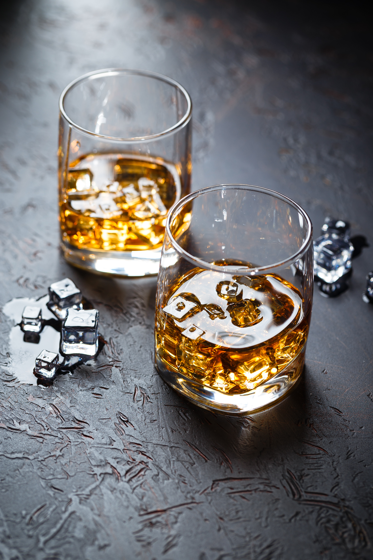 Whiskey on the rocks in two glasses on a dark background
