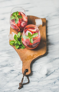 Blood orange and strawberry summer Sangria. Fruit refreshing rose wine cocktails in glasses with ice and mint on wooden board over grey marble background, selective focus
