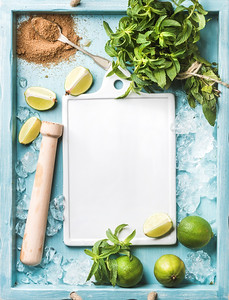 Ingredients for making mojito summer cocktail: chipped ice, mint leaves, brown sugar and lime with white ceramic board in center on turquoise blue painted wooden background. Top view, copy space