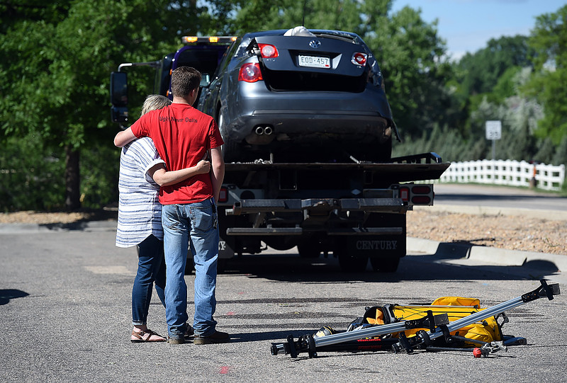 A unidentified teen driver and his mother embrace as they look at his car on a tow truck Wednesday, May 30, 2018, after a he ended up in the river on Namaqua Road in west Loveland. He was not injured in the accident.  (Photo by Jenny Sparks/Loveland Reporter-Herald)