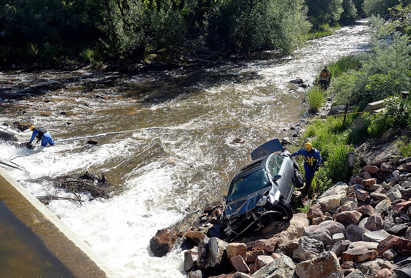 Loveland Fire Rescue Authority special operations team members Lt. Bobby Bartlett and Firefighter Braden Marker work to help a tow truck driver remove a car from the Big Thompson River  Wednesday, May 30, 2018, after a teen driver ended up in the river on Namaqua Road in west Loveland. The driver was not injured in the accident.  (Photo by Jenny Sparks/Loveland Reporter-Herald)