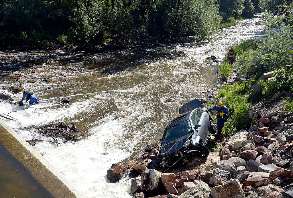. Loveland Fire Rescue Authority special operations team members Lt. Bobby Bartlett and Firefighter Braden Marker work to help a tow truck driver remove a car from the Big Thompson River  Wednesday, May 30, 2018, after a teen driver ended up in the river on Namaqua Road in west Loveland. The driver was not injured in the accident.  (Photo by Jenny Sparks/Loveland Reporter-Herald)
