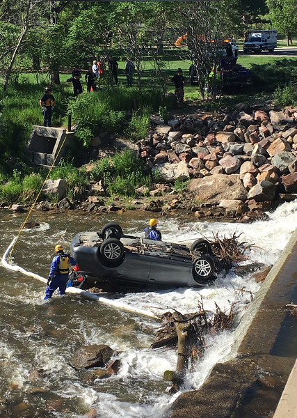 Loveland Fire Rescue Authority special operations team members Lt. Bobby Bartlett and Firefighter Braden Marker work to secure a car on its roof in the Big Thompson River so a tow truck can pull it out Wednesday, May 30, 2018, after a teen driver ended up in the river on Namaqua Road  in west Loveland. The driver was not injured in the accident.  (Photo by Jenny Sparks/Loveland Reporter-Herald)
