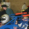 IRL DRIVER SARAH FISHER LOOKS ON AS HER BROTHER-IN-LAW KYLE O'GARA STRAPS IN HIS #23 MIDGET AT THE RUMBLE IN FORT WAYNE.