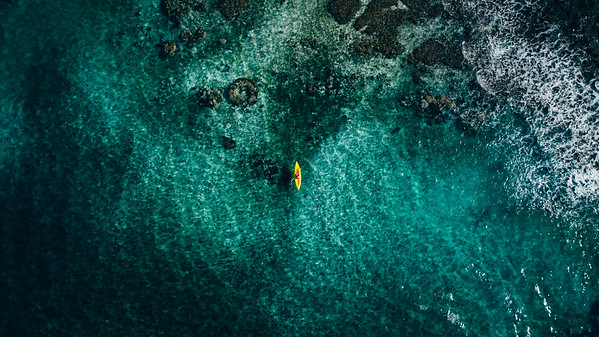 Aerial drone view of kayaker at Blackbird Caye at Turneffe Atoll in Belize