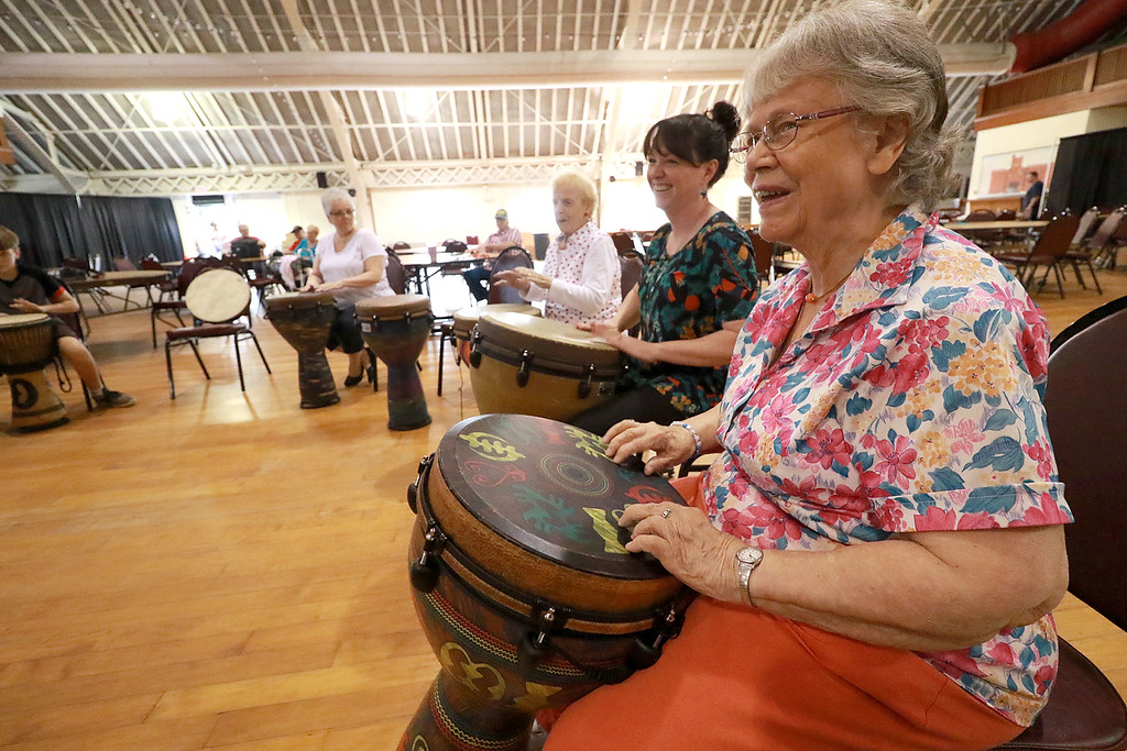 . The Fitchburg Senior Center had drum teacher Tim Kane in on Wednesday morning to teach a class in drumming. June Sears participates in the class at the center. SENTINEL & ENTERPRISE/JOHN LOVE