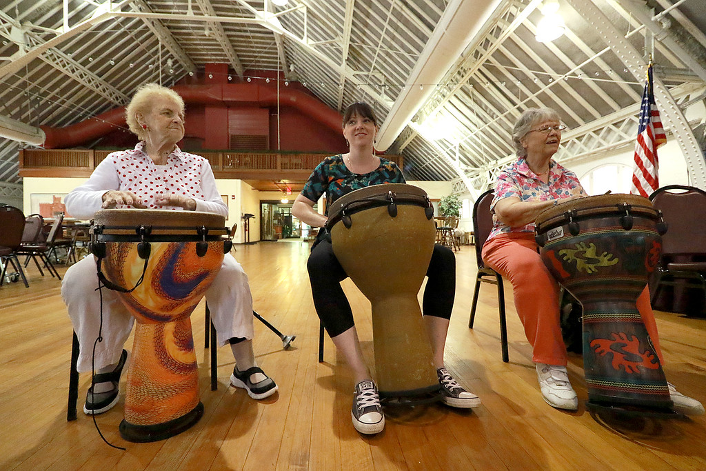 . The Fitchburg Senior Center had drum teacher Tim Kane in on Wednesday morning to teach a class in drumming. Josie Cormier, Erin Rice and June Sears participate in the class at the center. SENTINEL & ENTERPRISE/JOHN LOVE
