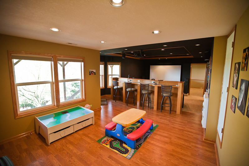 This is the view upon entering the downstairs from the main floor. Large play room can bee seen with a media room separated by an entertaining high bar. This floor has high end trim including hardwood finish work, doors, and crowns.  Plenty of daylight through six large windows and easily transforms into a home theater/media room with blackout blinds. A walk in storage door on the right leads to tons of additional pantry space. Lighting on this floor is controlled via a Graffic eye remote scene controller from the comfort of the seating in the media/theater room. A pellet stove warms the entire floor on cold nights (stove negotiable).