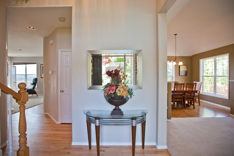 View upon entering the home. The family room is pictured to the left and the Front room and dining room can be seen to the right. Immediately on your left is the staircase to the upstairs. Hardwood floors have been refinished and are immaculate, new carpet in the family room. Both the entryway and rooms to the right are soaring vaults.