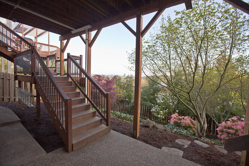 This is the view from the backyard patio and staircase descending from the upper deck. The back Patio stretches the entire length of the home in exposed aggregate. Lots of area to play, sit, or add additional amenities (hot tub, etc). A fenced dog run is also hidden on the Patio and is covered from the elements.