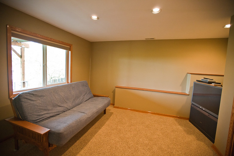 Alternate view of the downstairs fourth bedroom. A unique hardwood shelf can be seen on the rear wall for display or storage.
