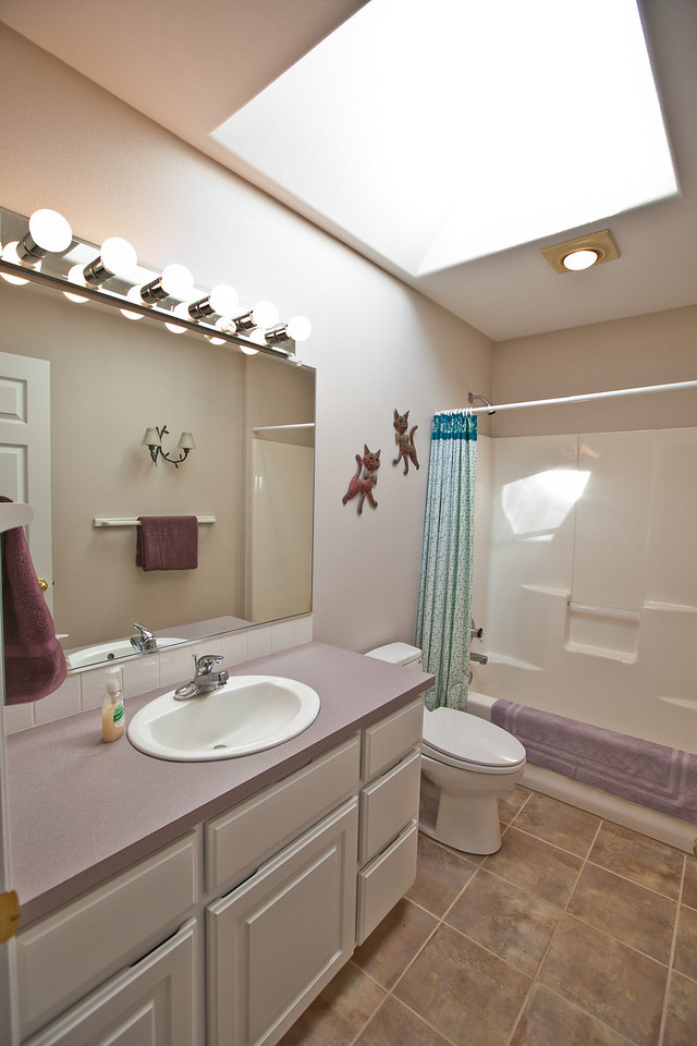 A view of the upstairs second full bathroom. New tile floors and upgraded toilets (toto) have been installed in both upstairs bathrooms. A large skylight allows for great natural daylight.