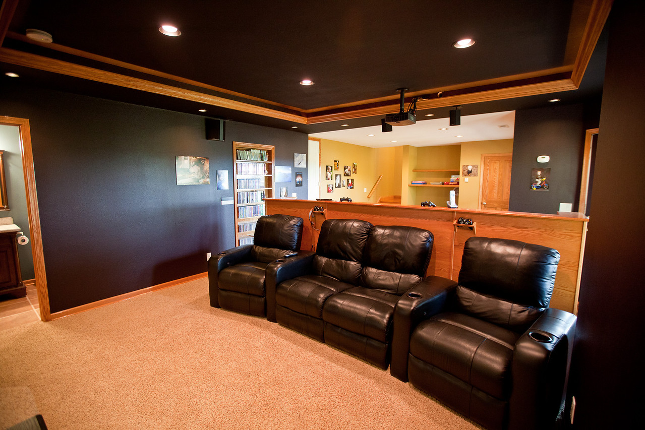 This is a view of the media and play room from the theater side. The bathroom can bee seen to the left and the media control room to the rear on the right. A nook sits off view to the right that leads to a door to the backyard. All new floors on this level of the home.