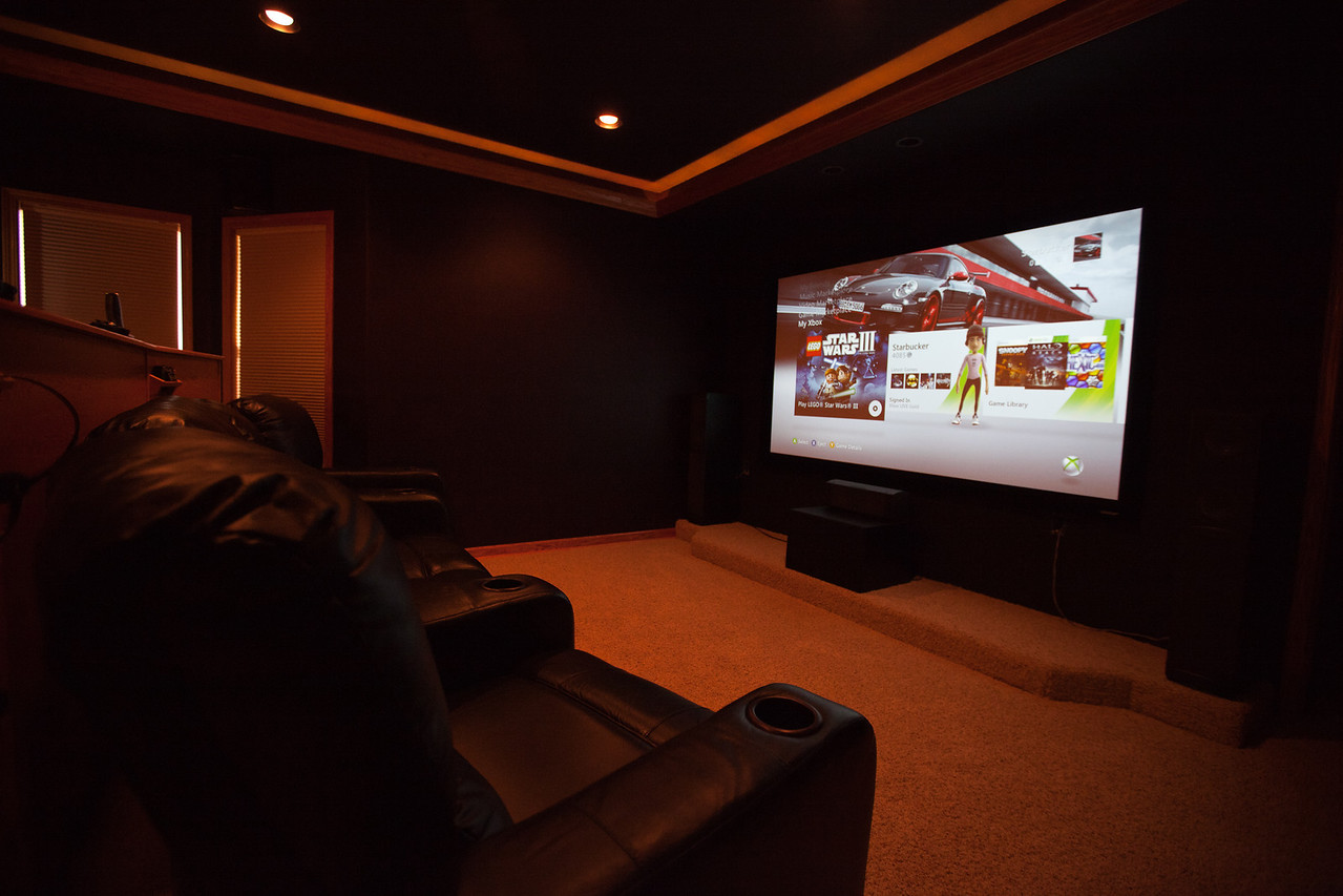 This is a view of the media room in use. The 100 in high definition screen is gorgeous. (screen and projector are not included in the sale but are negotiable). Note the soffit lighting illuminating from the hardwood crowns provides the perfect amount of ambient light for watching movies, video games, or surfing the web.