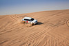 Sand flying everywhere as 4x4 land cruisers skid across the Arabian Desert.