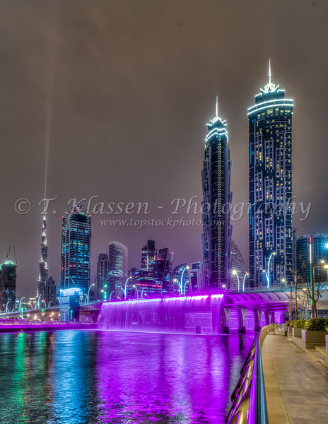 A view of tall buildings in the Business Bay area illuminated at night in Dubai, UAE, Middle East.