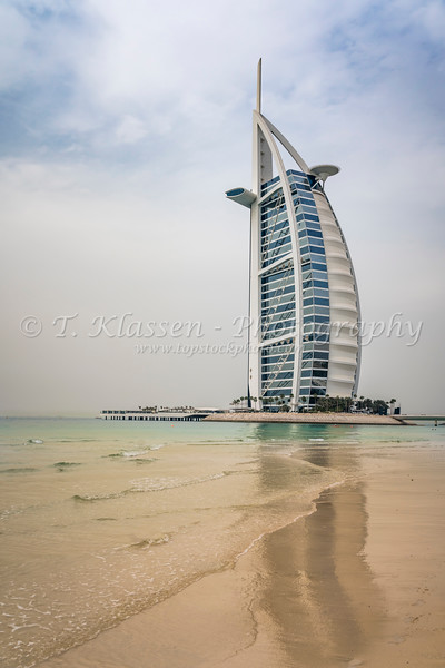 The Burj Al Arab Hotel and reflections in a sandy beach in Dubai, UAE, Middle East.