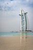 The Burj Al Arab Hotel and reflections in a sandy beach in Dubai, UAE, Middle East.