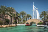 The Madinat Jumeirah canal and waterway with the white Burj Al Arab in Dubai, UAE, Middle East.