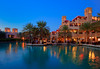 The Madinat Jumeirah souq buildings illuminated at night in Dubai, UAE.
