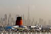 The Dubai city skyline and the Queen Elizabeth II ocean liner in Dubai harbour, UAE.
