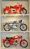 Motorcycles are displayed in unusual ways. The flow of the displays varies, this photo is from a wall of small Italian machines.  The Ducati on the bottom is rare and unusal - it's an oil in the frame model