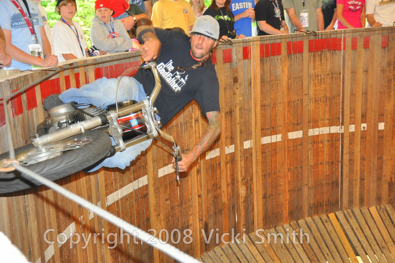 Rhett does it the old fashioned way in his genuine board track race track built in 1941.  He rides the walls right up to the guidewire.  It's really something to see, is genuinely entertaining and fits the vintage motiff perfectly by making history come alive.