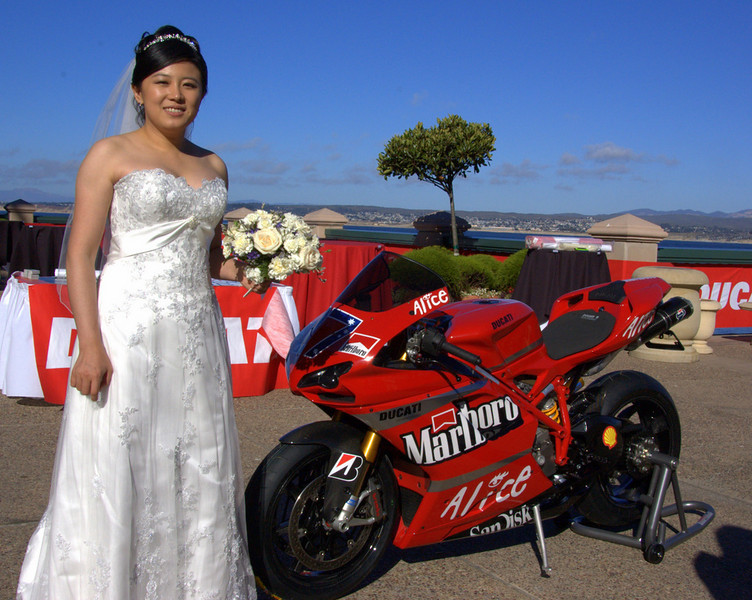 "Saturday night there was a ""Thank you for all you do"" party for the US Ducati Owners Clubs (DOC). Since Casey Stoner was expected to attend it seemed like a good idea to invite John Bragg to bring his Stoner replica 1098 to the party. It attracted a crowd as soon as it arrived and this bride took a moment from her wedding to have her photo taken with it."