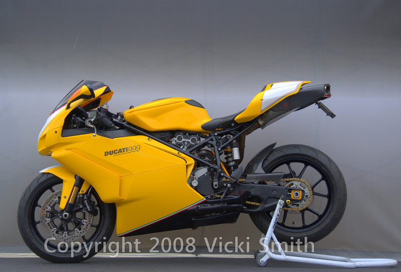 That's John Avelluto's 2005 999, all clean and fresh off the 1600 mile Iron Butt from Kansas City to Daytona through temps as low as 17 degrees. Here's his bike card:<br />  1 of 31 yellow 2005 999's imported in 05. This one was treated to what should have been done from the factory. All of the components that were once silver or gray are now blacked out, by methods that are factory correct. Also there are painted number boards and tri-color stripes that represent the colors of the Italian flag, birth place of this beautiful machine. Every square mm of this motorcycle has been gone over. Most of the work was carried out  personally even though I am not a m/c shop owner or a high performance parts vendor/dealer, just a pizza man with a great passion for Ducati! and I feel like this shows. This machine is ridden daily and was rode here to Daytona from Kansas City non stop for this event.