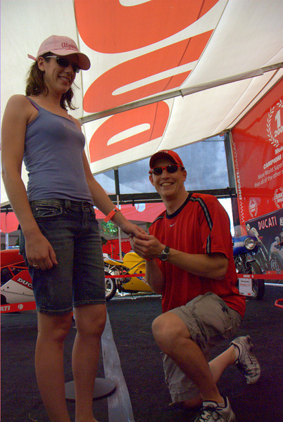"That's Kevin Drum and Amy Chraston. Kevin knew he was going to propose to Amy sometime over the Mid Ohio weekend. After two years of dating, he was sure she was the one. Maybe the gift of a custom made Ducati Corse necklace was the last sign he needed, or it could have been that she knows each of his three Ducati's almost as well as he does. Whatever the reason, he had the ring all ready and was just waiting for the right time. That time came in the middle of the Ducati Superbike Concorso tent Saturday afternoon - in a completely spontaneous moment, surrounded by a room full of Ducati's, Kevin asked Amy to marry him and she said yes, much to the delight (and surprise) of the people all around.<br /> Showing off the necklace Amy bought him, Kevin said he bought his first Ducati in 2000 and now has three, all highly modified - a 748, 996R and 1098 Tricolore.  When asked ""Why here?""  He said I'm the Ducati guy, it's what I love and this just seemed like the right place""<br /> Oddly enough, it's the second proposal, there was one at the Laguna Seca round as well. Maybe it's in the Ducati water! Ladies, if your Ducati guy needs a little push, next round is Indianapolis Motogp!"