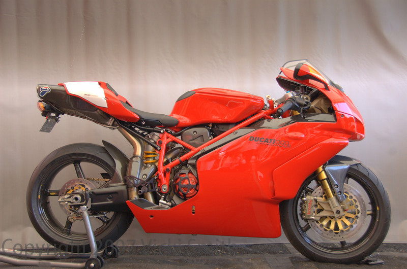 "Jack Newell sent this over the top 999R from Louisiana to take home the top prize in Modified. This one's in the dictionary under ""sleeper"". Here's the description, see for yourself:<br /> <br /> 2005 Ducati 999R<br /> <br /> This 999R Superbike has many performance modifications designed to enhance the overall level of performance and sophistication of the machine while still closely resembling a factory prepared Ducati motorcycle. <br /> <br /> Modifications include:<br /> <br /> Termignoni 57mm Full system exhaust with Titanium canister & racing ECU along with a fully custom mapped Dynojet Power Commander, properly setup and blue-printed fuel-injection system and large diameter carbon fiber racing air ducts to fully optimize performance and rideability through the billet quick-turn racing throttle.  An STM slipper clutch and billet clutch slave cylinder with a Ducati Performance vented clutch cover allows for improved corner entry on both street and track and the proper dry clutch sounds to be thoroughly enjoyed through the rare corse style vented magnesium clutch side cover!  With a dyno-tested and very real 150 horsepower at the rear wheel, this is a very acceleration happy 999R! <br /> <br /> Building on an already excellent platform, weight savings, handling and looks have been improved with the addition of beautiful and lightweight BST carbon fiber 5-spoke wheels, Titanium wheel axles, 520 chain & sprocket conversion with a Regina gold-link racing chain and 15/40 gearing.  Beautiful billet 27mm triple clamps in conjunction with the steering angle set to 23.5 degrees, properly setup ride height, swingarm length, revalved and properly sprung Ohlins suspension with hydraulic preload adjustment on the rear shock achieve a very light steering motorcycle while still retaining the legendary Ducati stability.  <br /> <br /> The braking system is a highlight of the 999R and is of World Superbike caliber.  Rare & exquisite Moto Corse Racing billet fork lowers with 108mm caliper spacing and remote compression adjustment for the Ohlins fork.  With Brembo monoblock radial racing 4-pad calipers (titanium pistons)  Brembo full-floating 320mm SBK rotors and Brembo GP radial pump master cylinders (both brake and clutch) along with Rizoma billet remote reservoirs and remote brake lever adjusment capability allows the 999R to stop as well as it goes, if not better!  Rear braking is enhanced with a Moto Corse under-slung billet caliper bracket for the Brembo Endurance style P4 24 4-piston billet race caliper with a Brembo full-floating rear disc and Rizoma billet reservoir. <br /> <br /> Following the theme of less weight, additional carbon fiber components were added - the original plastic tailsection has been replaced with factory Ducati carbon fiber pieces, along with front and rear carbon fiber fenders and trim pieces to accent the factory magnesium bits.  Fully adjustable billet Acculign rearsets and shift/brake levers improve looks and rider comfort while quite a few titanium fasteners are used throughout the 999R as well as a titanium Ducati Performance fuel cap.  Moto Corse Titanium radiator and oil coolers screens protect their components while looking gorgeous.  The cooling system has been enhanced with a Speedymoto billet water pump housing, Samco black silicone hoses and Engine Ice coolant to keep the 999R temperatures in check during the hot and humid New Orleans riding season!"