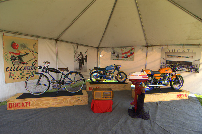 "A small historical display was organized under a tent in the entrance to the ""Island"".  That's a Ducati Cucciolo on the left, a Ducati radio, a 125cc Sport, a 5hp Ducati Cucciolo outboard engine and a 450 Desmo ""disc brake"".  (On loan courtesy of the Lambrechts-Smith Collection)"