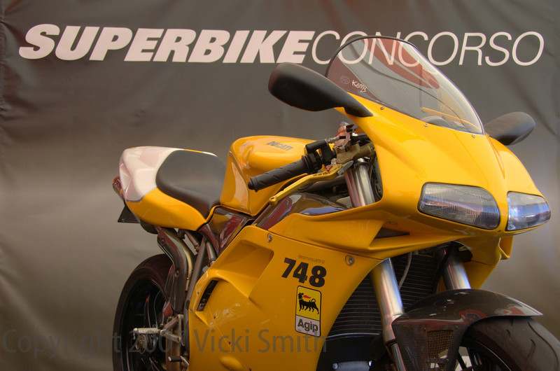 From the description card:<br /> Pure elegance, Pure Ducati!  From a stock 748, this master piece has been transformed into a one of a kind work of art.  Signed by Troy Bayliss and Ben Bostrom. Added:  black 5 spoke marchesinis, carbon fiber and the monoposto tail. Carbon fiber list: Handle bars, air intake duct, front fender, radiator cover, clutch cover, sprocket cover, air box, heel guard, exhaust guard, chain guard, under seat tray, and 3/4 Leo Vinci carbon exhaust system.