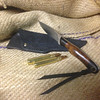 "This pic shows the Knife with it's ""Rough Out"" sheath and a couple 375 Ruger solids."