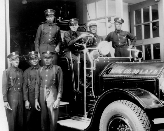 Firemen of Engine Company No. 30 Los Angeles Fire Department (LAFD) pose around a firetruck