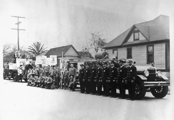A youth club in support of the fire department stand next to the men of Engine Company No. 30