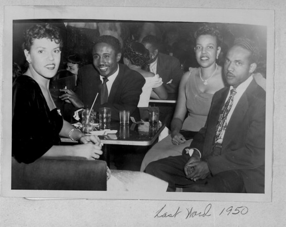 Four people sitting together at a table in the Last Word Club, 1950