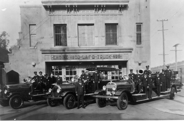 Firemen of Engine Company No. 30 pose on three fire trucks in front of the firestation