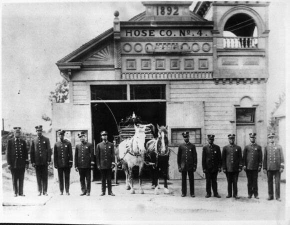 Firemen of Hose Company No. 4 pose in front of the station