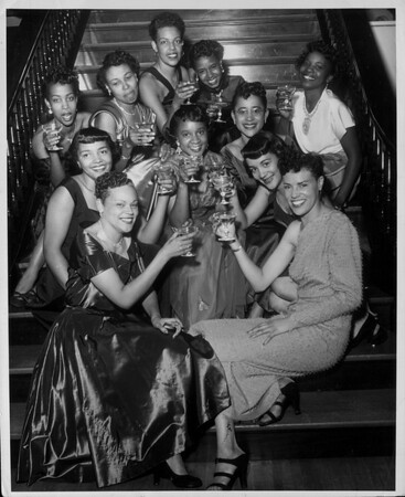Women of the Hour Social Club have a toast as they sit on the stairway of the Elks Ballroom