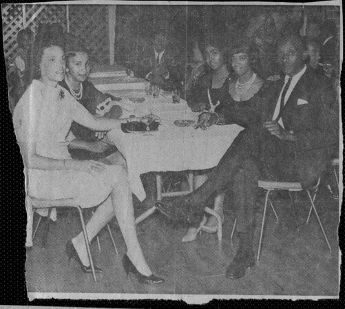 A nicely dressed group of people sitting at a table in the Elks Hall