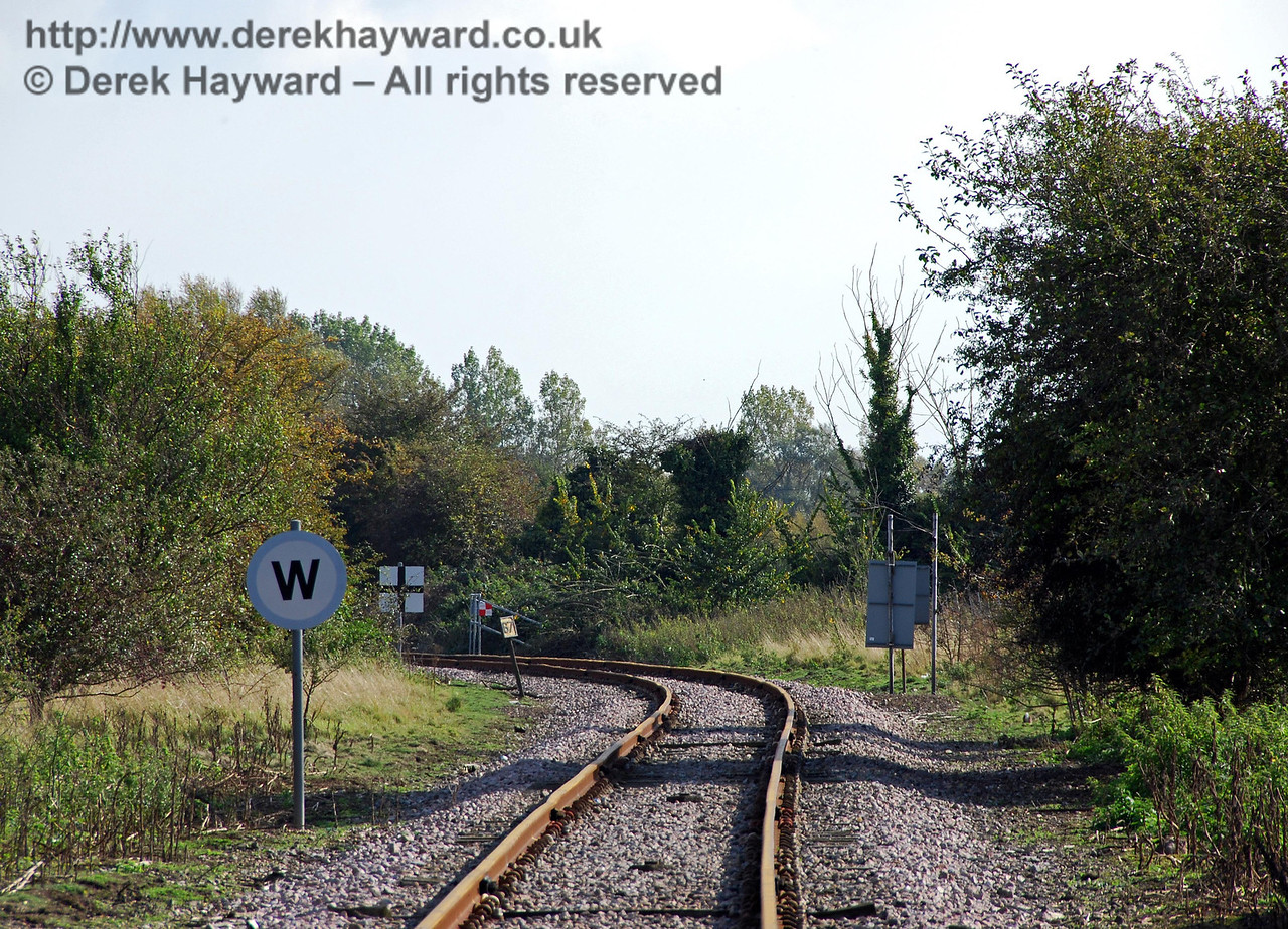 Looking south from King Street Crossing with a long lens.  The next road crossing is at the former Brooklands Halt, but the Whistle sign and crossing warning board probably refer Hobbs Public Bridleway (Old House Lane) which crosses the track around the bend, north of Brooklands Halt. 08.10.2008  This area is covered in a separate gallery.
